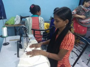 young woman learning to sew in vocational tailoring program from Remedia E3 job growth and rotary